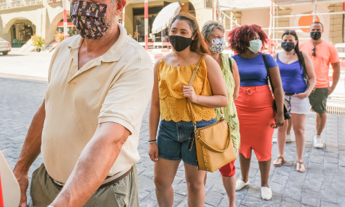 A line of people wearing masks.
